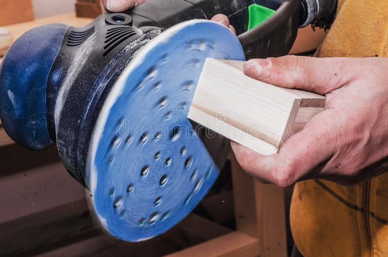 Hands a man polishes a wooden part with a grinding machine. Carp stock photography