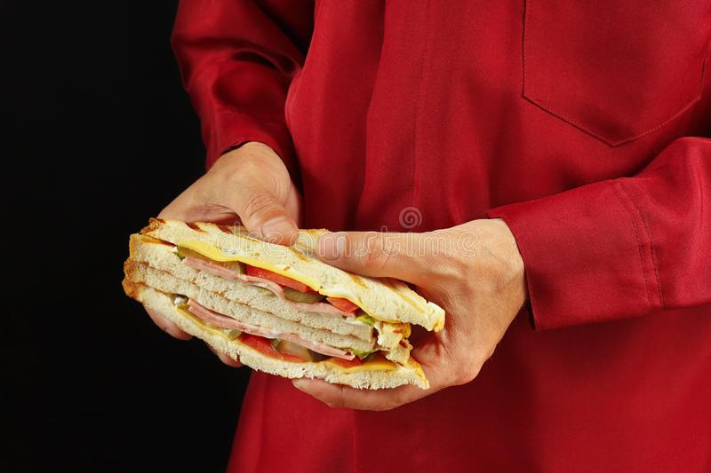 Hands of man in a red shirt with a double sandwich on black background. Hands of man in a red shirt with a double sandwich on a black background royalty free stock photos