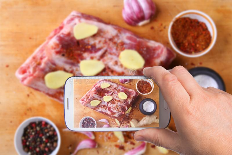 Hands of man with smartphone taking photo Raw fresh meat, uncooked lamb or beef ribs with pepper, garlic, salt and royalty free stock photo