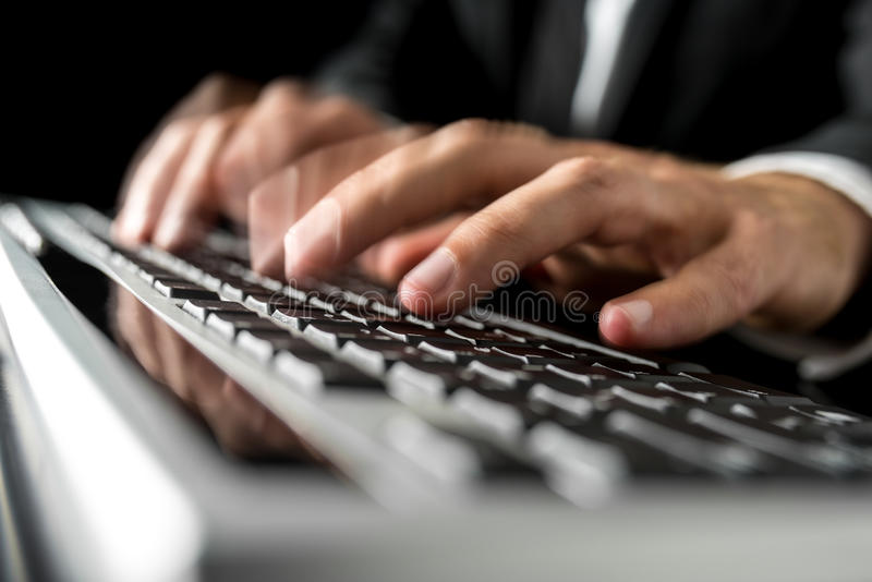 Hands of a man typing fast on a computer keyboard royalty free stock images