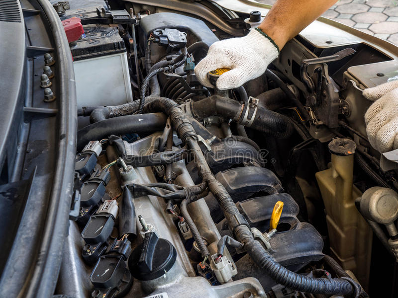 Hands man wearing white gloves of car mechanic working in auto repair service. He have fix old car engine streaked with dust and oil stains stock image