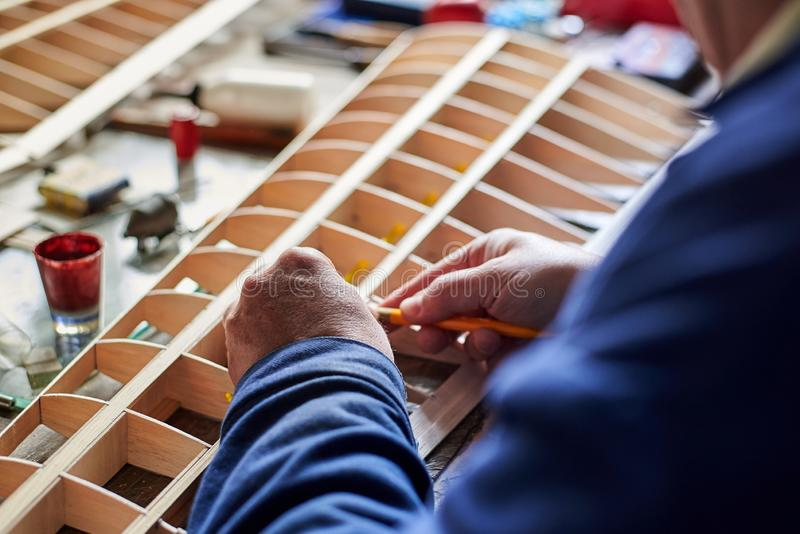 Hands of a man who makes the wing of a radio-controlled aircraft, the construction of the airplane. Hands of a man who makes the wooden wing of a radio stock image