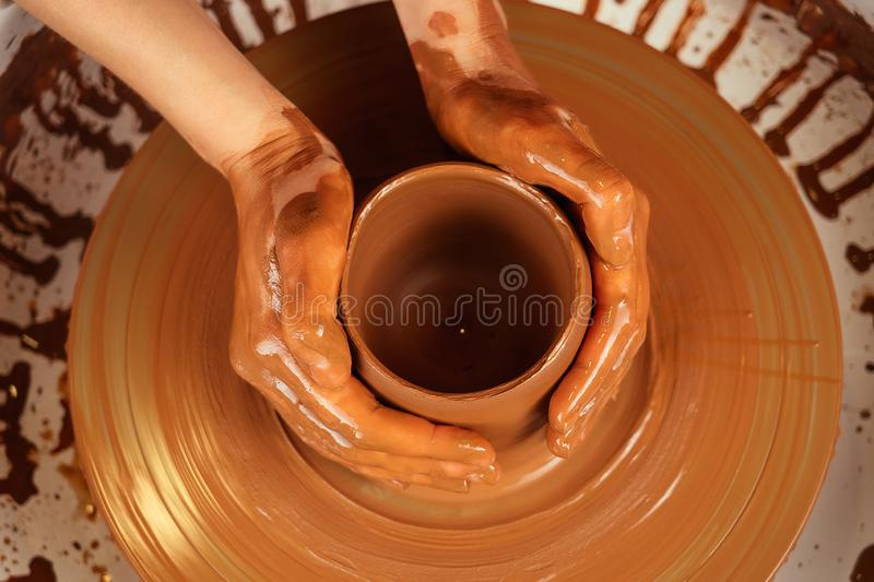 The hands of a man and a woman in clay on a potter`s wheel mold a vase. The potter works in a pottery workshop with clay stock photo