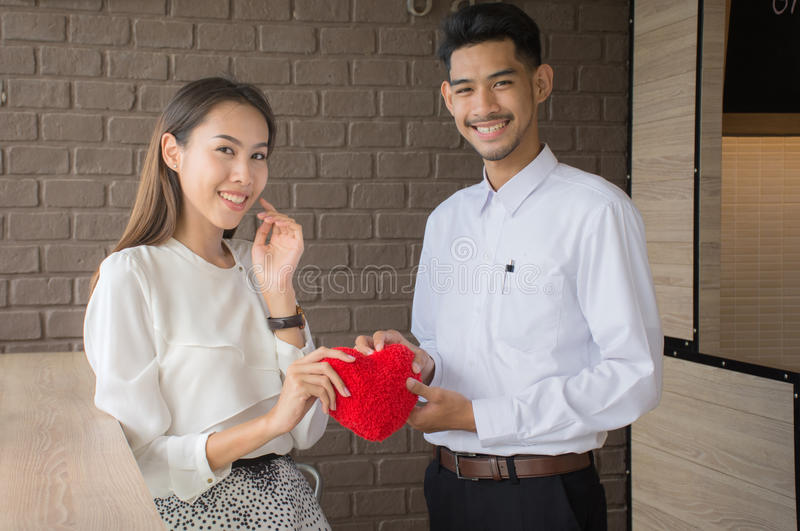 Hands of man and woman holding red heart protecting it together royalty free stock photography