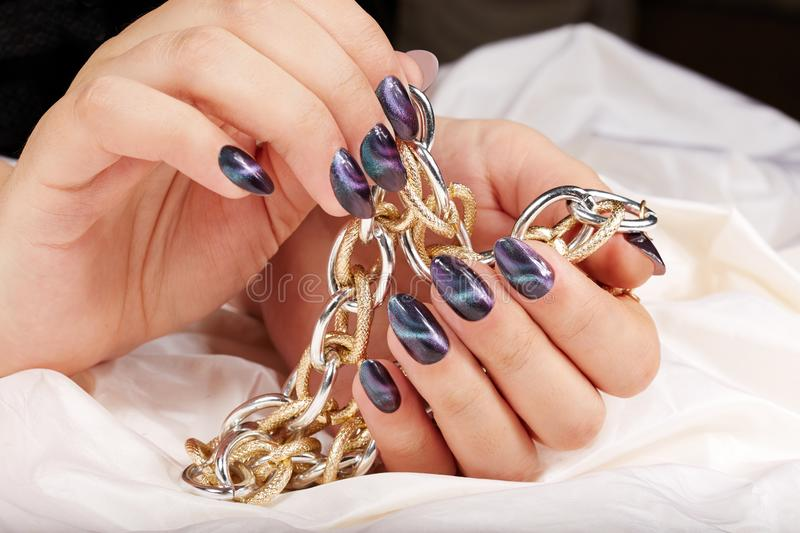 Hands with manicured nails with cat eye design holding a necklace. Hands with beautiful manicured nails with cat eye design holding a golden chain necklace stock images