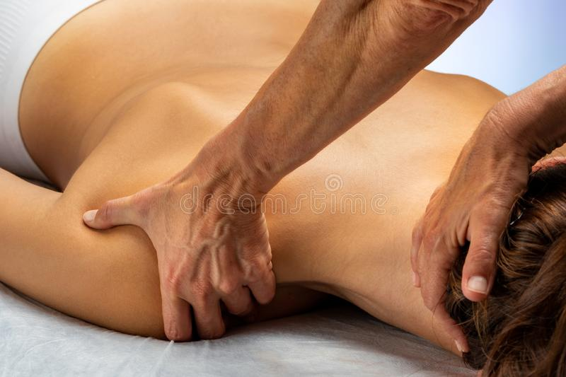 Hands manipulating neck and shoulder muscles on woman. Close up of hands manipulating neck and shoulder muscles on young woman. Girl laying on spa bed facing royalty free stock photo