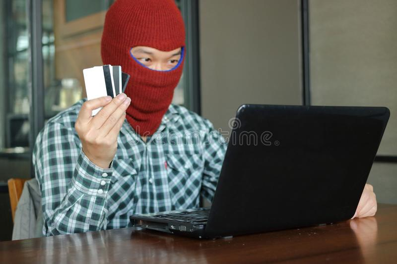 Hands of masked hacker wearing a balaclava holding credit card between stealing data from laptop. Internet crime concept. Hands of masked hacker wearing a stock photo
