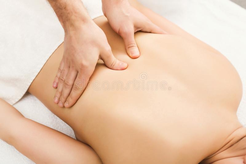 Closeup of hands massaging female shoulders and back royalty free stock photography