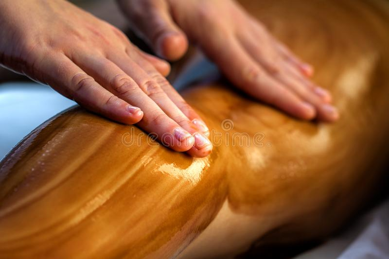Hands massaging female calf muscle with hot chocolate oil. Close up detail of hands massaging female calf muscle with hot chocolate oil royalty free stock photos