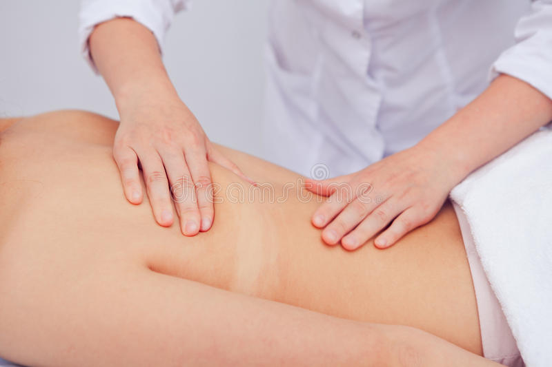 Hands of masseur massaging female back royalty free stock photography