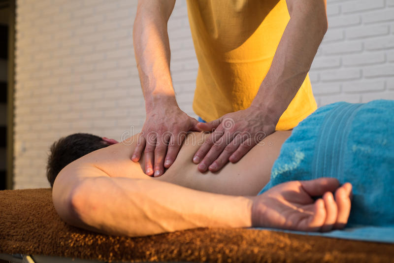 Hands of a masseuse. During massage back royalty free stock image