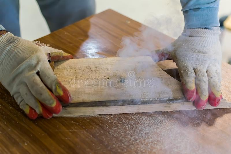 Hands of the master in gloves hold a wooden billet. While working on the milling equipment royalty free stock image