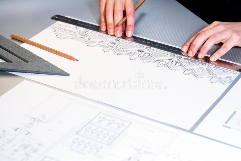 Hands measuring detail on house plans. stock photography