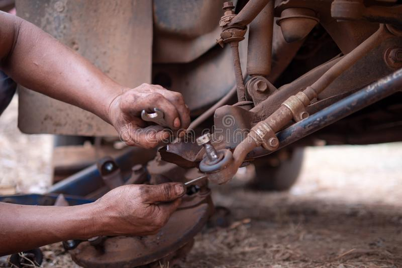 Hands of mechanic fixing wishbone control arm of the truck part to repair front wheel. Car, tire, service, workshop, garage, auto, black, automobile, wrench stock photos