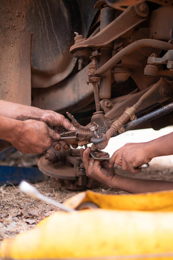 Hands of mechanic fixing wishbone control arm of the truck part to repair front wheel. Car, tire, service, workshop, garage, auto, black, automobile, wrench stock photo