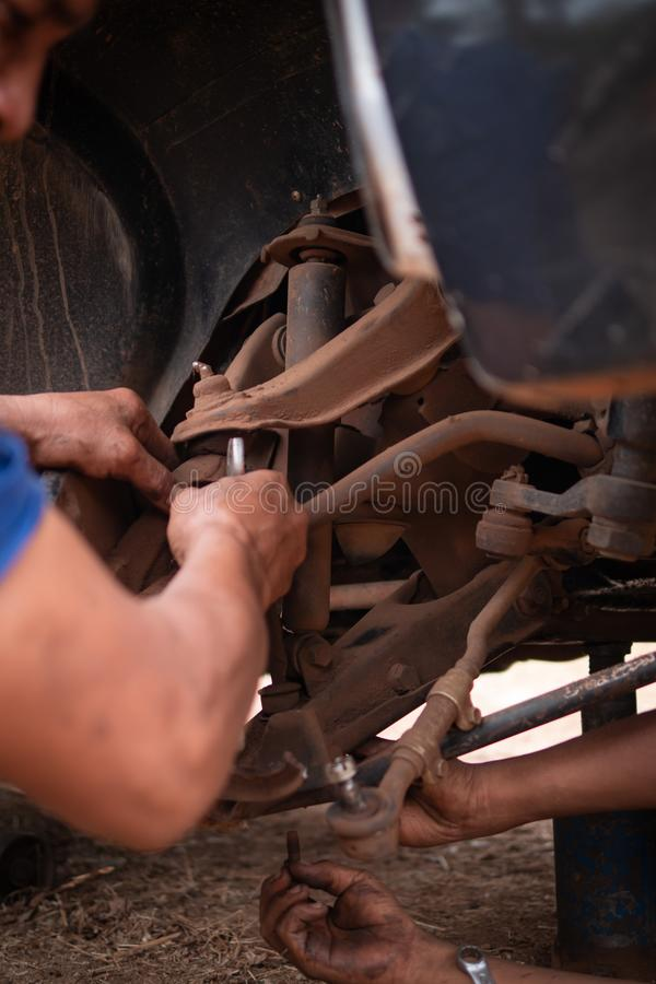 Hands of mechanic fixing wishbone control arm of the truck part to repair front wheel. Car, tire, service, workshop, garage, auto, black, automobile, wrench stock images