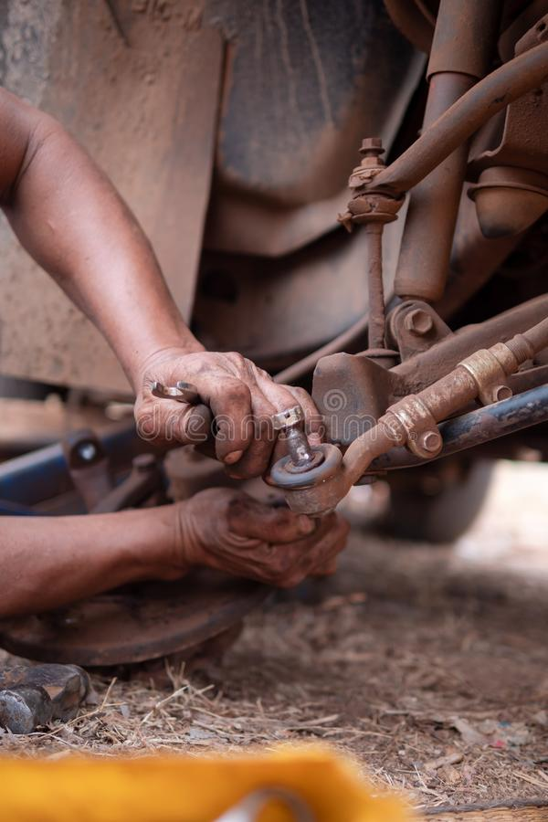 Hands of mechanic fixing wishbone control arm of the truck part to repair front wheel. Car, tire, service, workshop, garage, auto, black, automobile, wrench royalty free stock photos