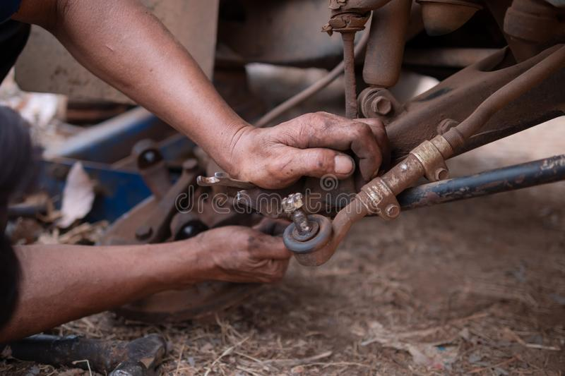Hands of mechanic touching wishbone control arm of the truck to fix and repair front wheel. Car, tire, service, workshop, garage, auto, black, automobile stock image