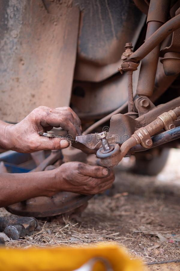 Hands of mechanic touching wishbone control arm of the truck to fix and repair front wheel. Car, tire, service, workshop, garage, auto, black, automobile royalty free stock photography