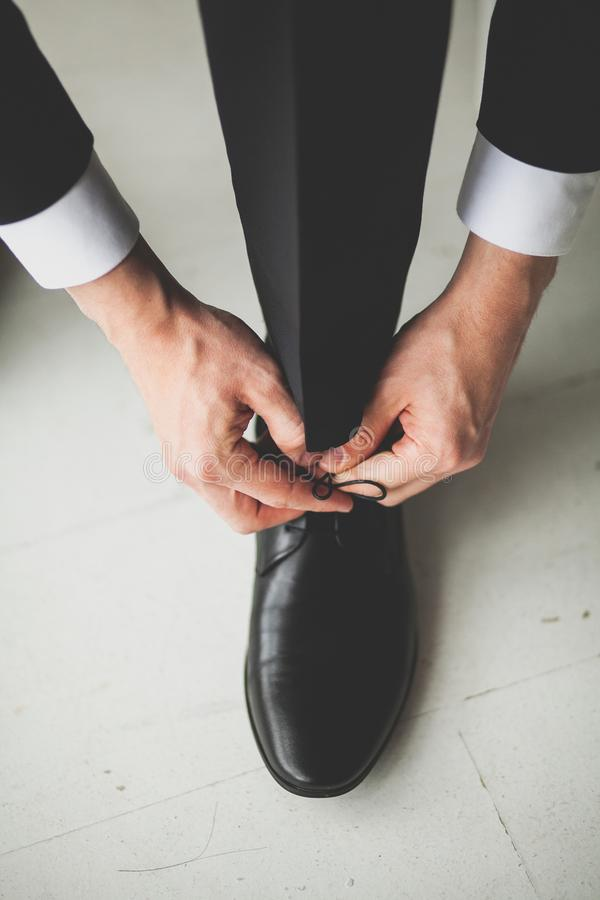 Hands men, groom, businessman tying the laces of his new black leather business shoes, close-up. The concept of business, royalty free stock photo