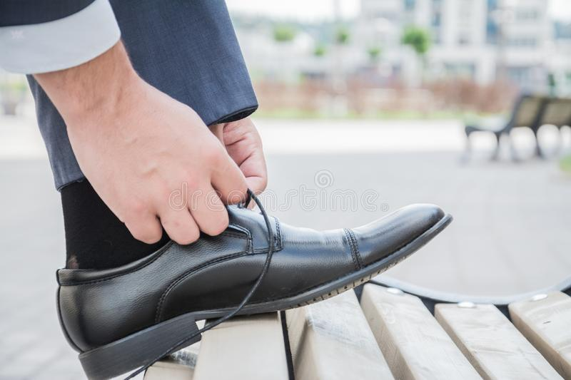 Hands men, groom, businessman tying the laces of his new black leather business shoes, close-up. royalty free stock images