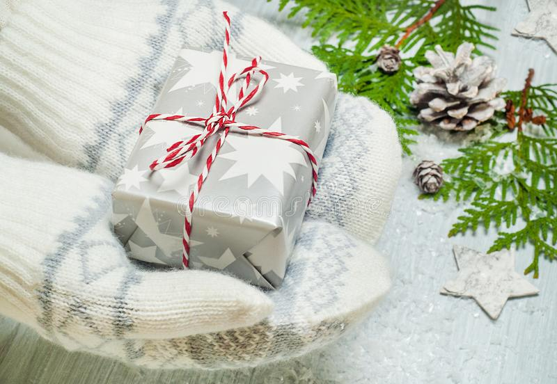 Hands with mittens holding a gift box. Christmas holiday concept. Hands with mittens holding a gift box. Christmas giving concept stock photo
