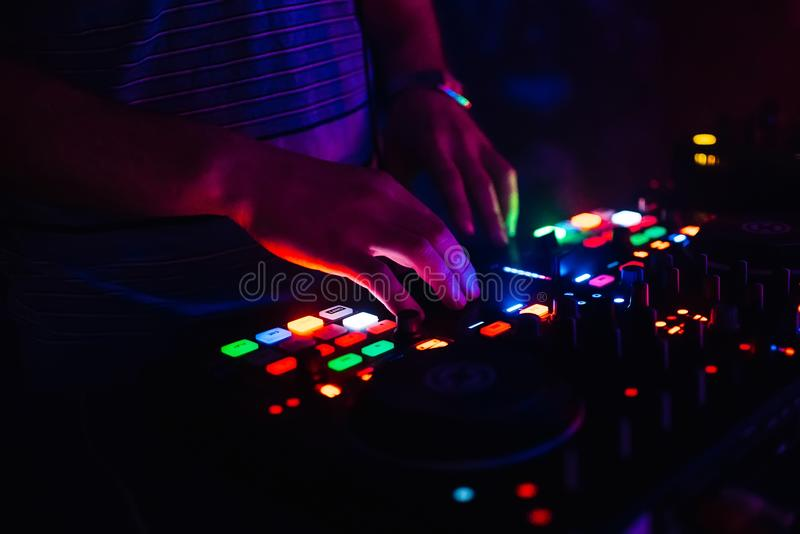 Hands of modern DJ professional mixer and music Board of the controlling buttons and levels stock image