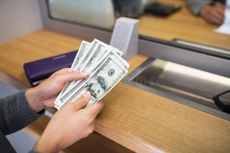 Hands with money at bank or currency exchanger. People, withdrawal, saving and finance concept - hands with cash money at bank office or currency exchanger royalty free stock photo