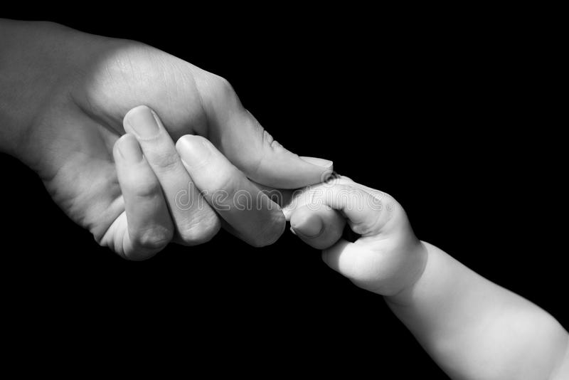 Hands of mother and baby closeup. Black and white stock photo