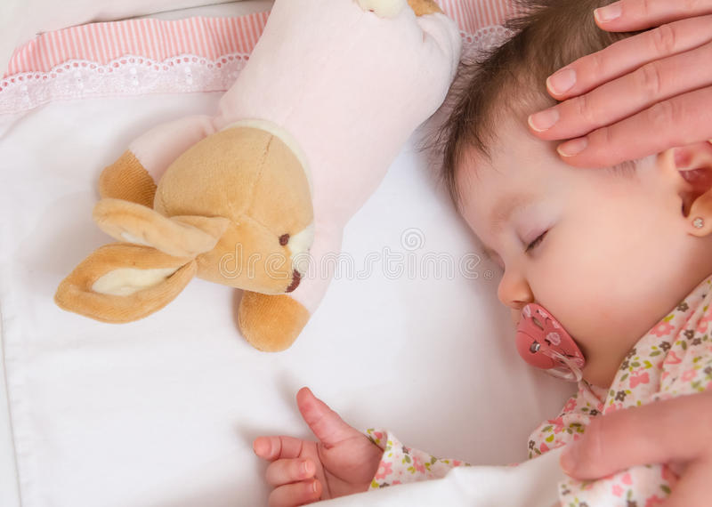 Hands of mother caressing her baby girl sleeping. Hands of mother caressing her cute baby girl sleeping in a cot with pacifier and stuffed toy stock photo