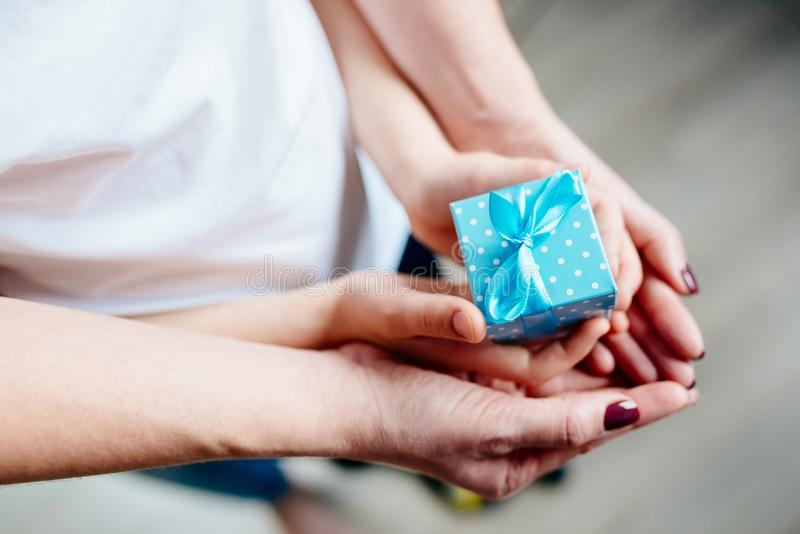 Hands of mother and child holding little box stock photo