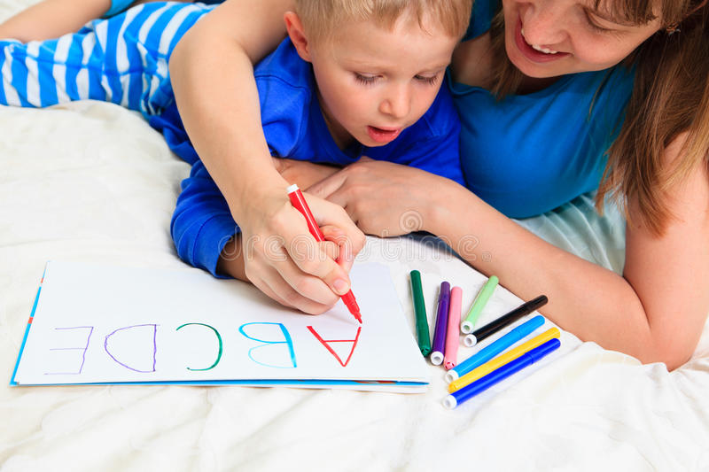 Hands of mother and child writing letters. Education and learning stock image