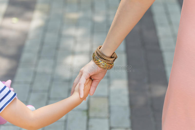 Hands of mother and daughter hold each other during city walk. royalty free stock photos