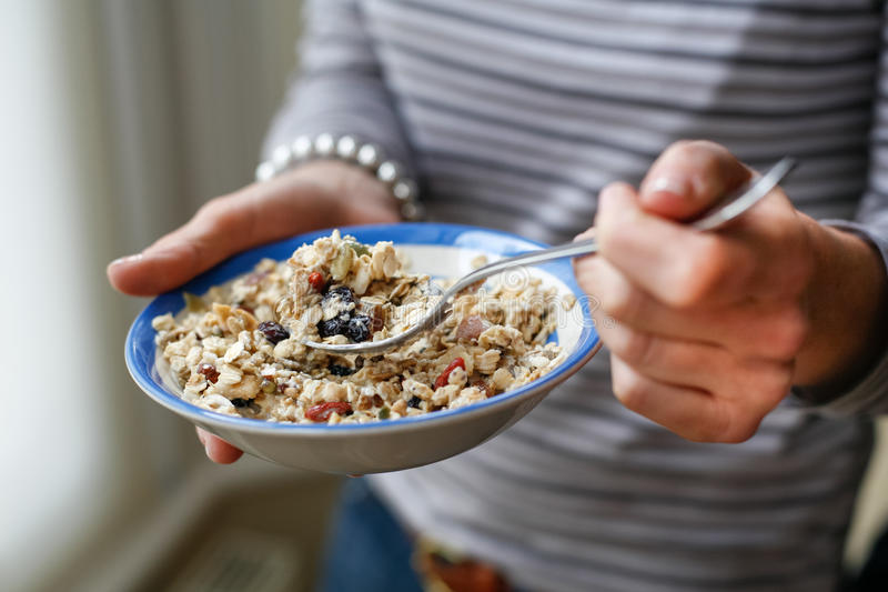 Hands and muesli. Hands of a woman holding a bowl with muesli royalty free stock image