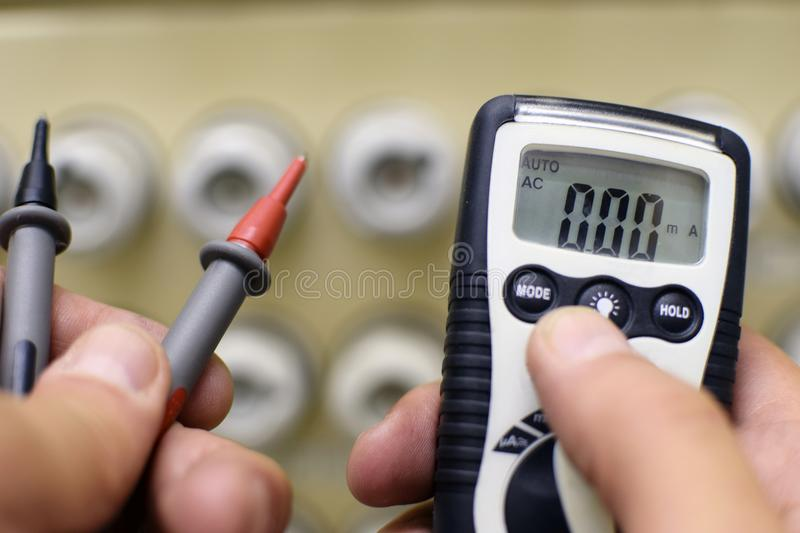 Hands with multimeter in front of the old fuse box royalty free stock photo