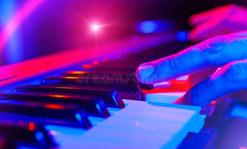Hands of musician playing keyboard in concert with shallow depth royalty free stock photography