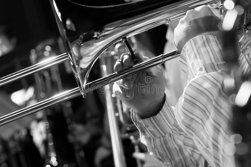 Hands musician playing the trombone in the orchestra. Closeup in black and white royalty free stock photography