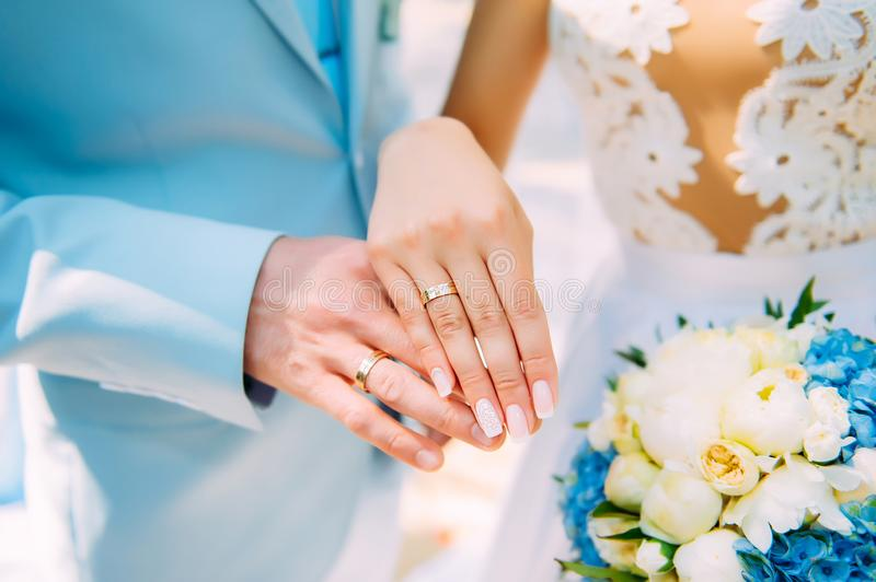 Hands of newlyweds with beautiful gold rings, close-up. White bridesmaid dress, bouquet, stylish manicure. Perfect wedding. Ceremony royalty free stock photo
