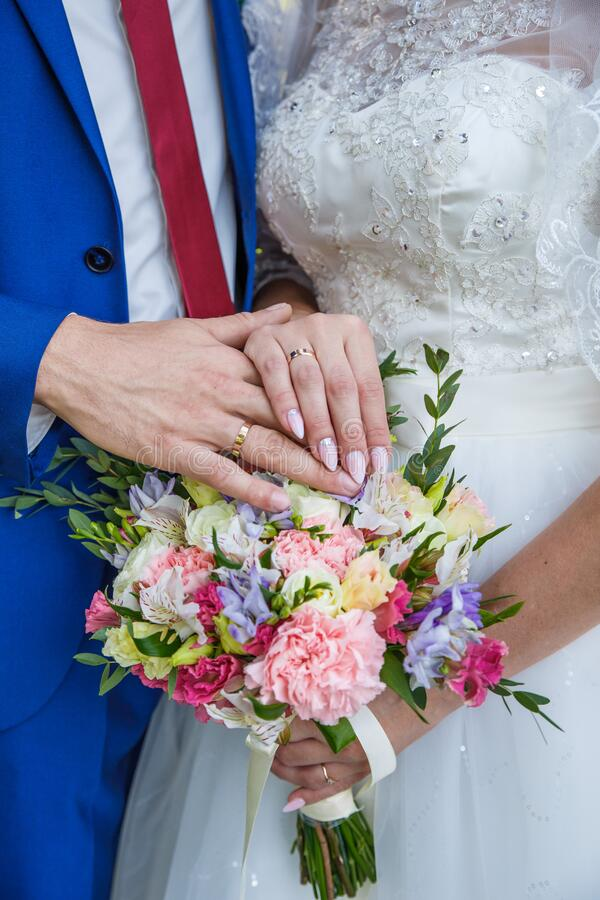 Hands of newlyweds with wedding rings and a bouquet of flowers. The groom in a blue suit and red tie. The concept of royalty free stock image