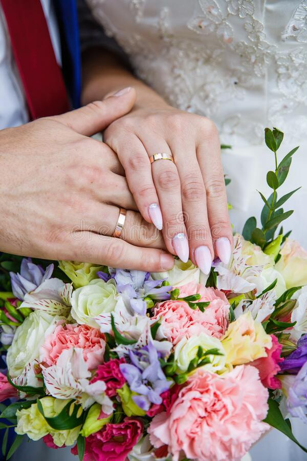 Hands of newlyweds with wedding rings and a bouquet of flowers. The groom in a blue suit and red tie. The concept of royalty free stock photo
