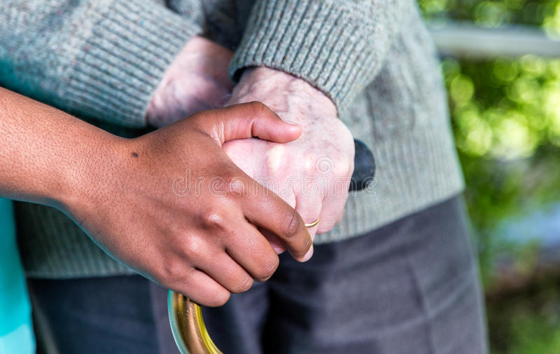 Hands of nurse and elder man with stick. Caregiver and retirement concept stock photography
