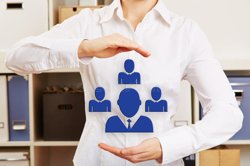 Hands in office holding network symbol. Hands of a business woman in office holding a network symbol with icons of people group stock image