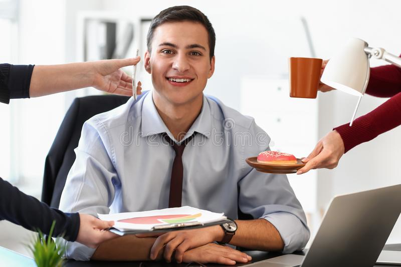 Hands of office workers offering their colleague to make choice between work and rest stock photography