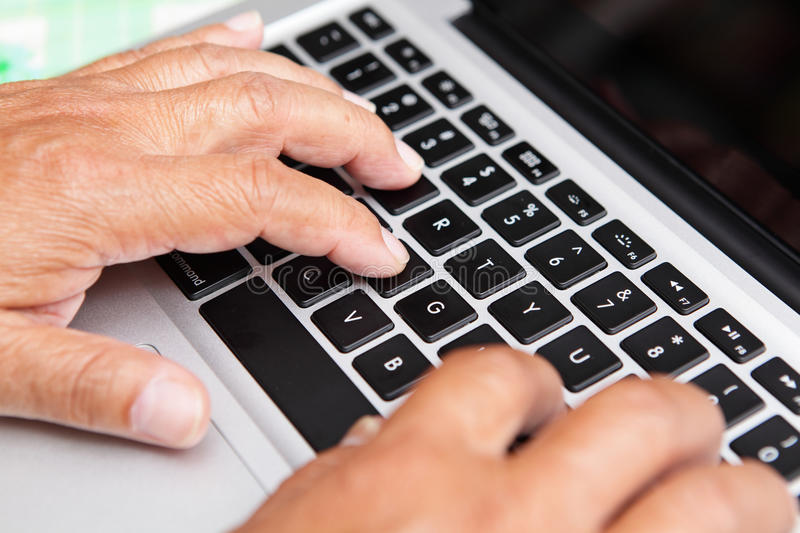 Hands of old man on computer royalty free stock photo