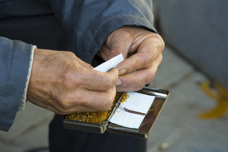 Hands of the old man are twisting tobacco cigarettes. The hands of the old man are twisting tobacco cigarettes stock photos
