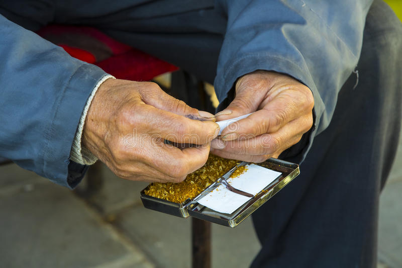 Hands of the old man are twisting tobacco cigarettes. The hands of the old man are twisting tobacco cigarettes royalty free stock image
