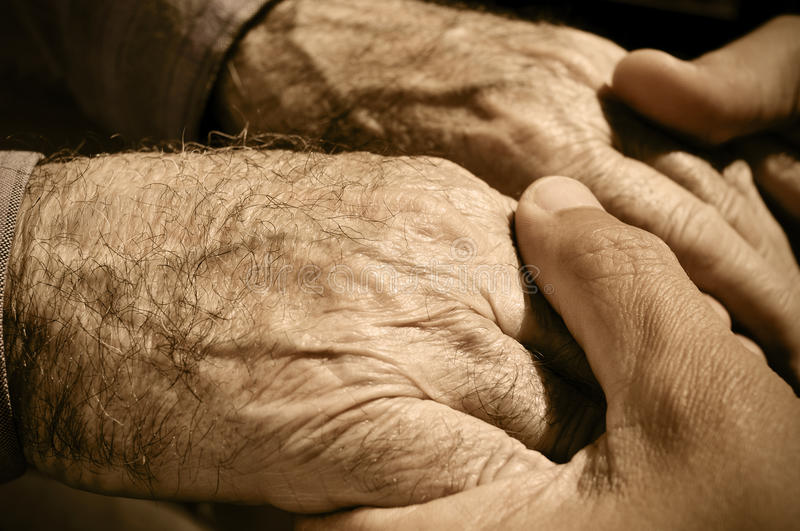 Hands of an old man. Young man holding the hands of an old man royalty free stock photos