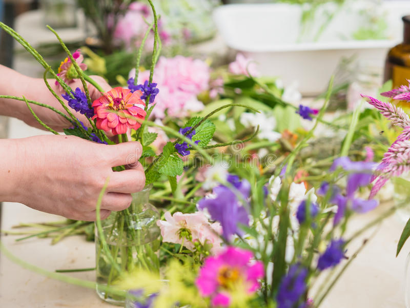 Hands of old woman arranging flowers. stock photography