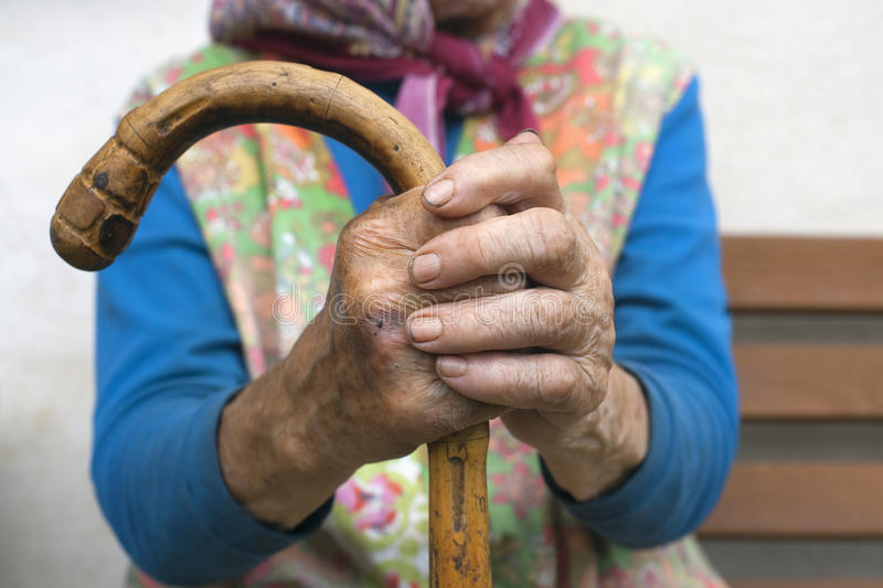 Hands of an old woman with a cane. Hand of an old peasant woman holding a walking stick royalty free stock photo