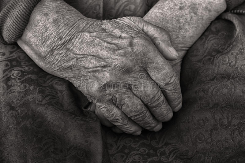 Hands of an old woman folded in her lap, black and white stock photo